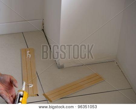 Carpenter on work putting wood skirting board