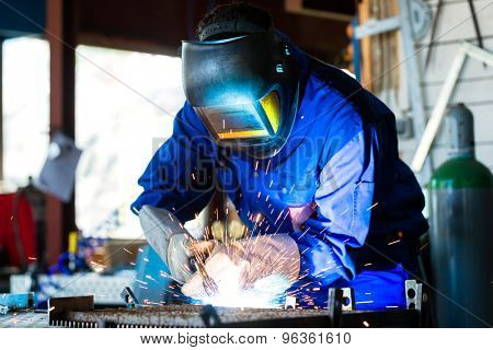 Welder bonding metal with welding device in workshop, lots of sparks to be seen, he wears welding googles