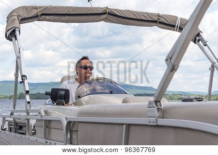 mature men driving a pontoon boat on a lake