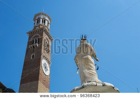 Low angle shot of Torre dei Lamberti in Piazza delle Erbe in Verona, with Marble statue in the foreground.