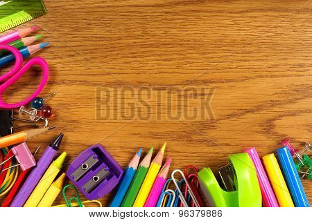 School supplies corner border on wood desk