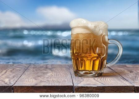 Glass of beer on empty wooden table with blurred sea on background, natural background with bokeh