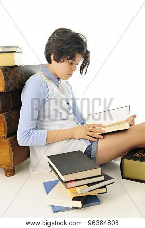 Vertical image of a young teen sampling one book while surrounded by many.  On a white background.