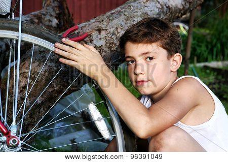 cute preteen boy make rapairment of his bisycle