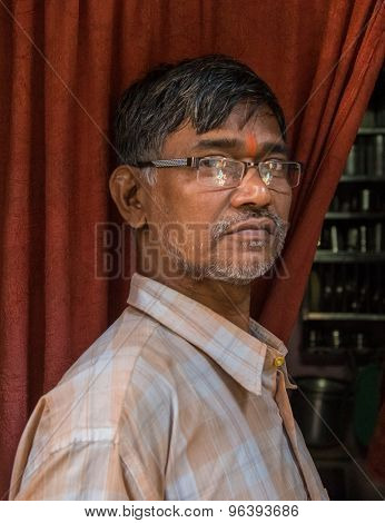 MUMBAI, INDIA - 12 JANUARY 2015: Elderly Indian man with glasses and bindi stands in doorway of home.