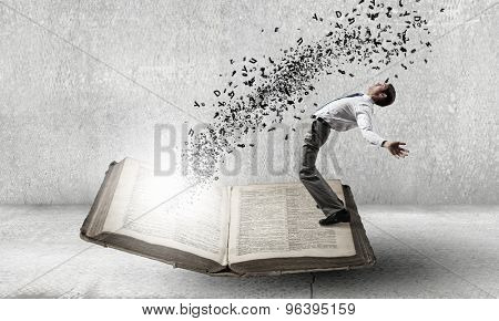 Young man benting to evade characters flying from book
