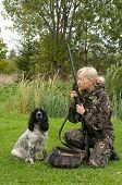 Blonde in camouflage with a gun and russian hunting spaniel. poster