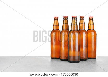 Bottles of beer on table against white background