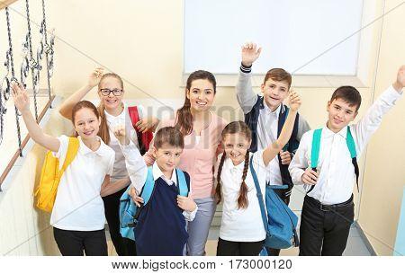 Teacher with children in school corridor during class break