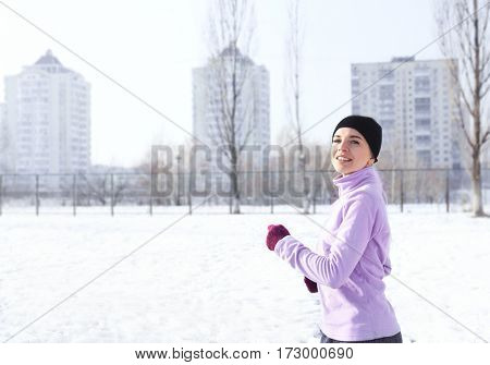 Sportive young woman running in winter morning poster