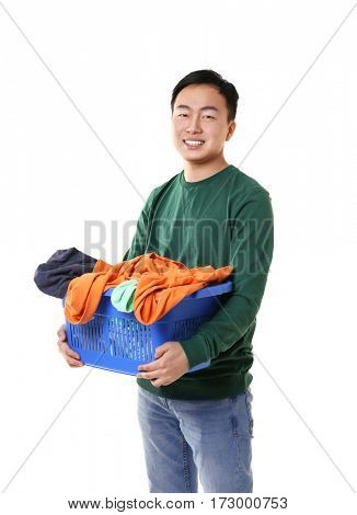 Happy Asian man holding plastic box with clothes on white background