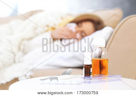 Set of medicines and electronic thermometer with blurred ill woman on background