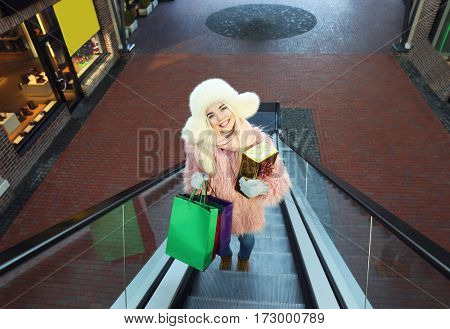 Woman with gift box and shopping bags on mall escalator