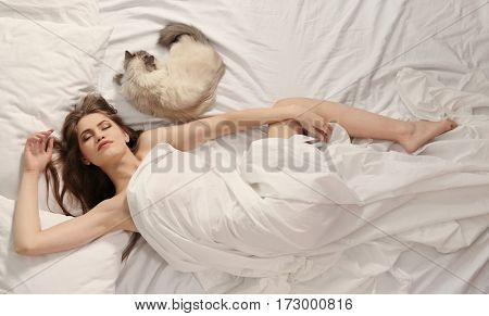 Beautiful young woman with cute cat lying in bed at home