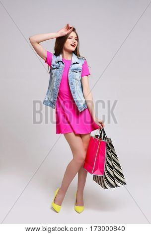 Beautiful young woman with paper bags on color background
