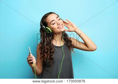 Beautiful young woman in headphones listening to music on light background