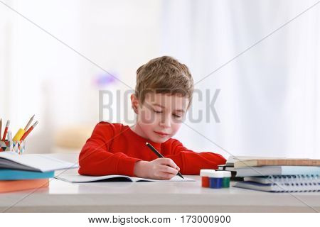 Schoolboy doing homework at table in room