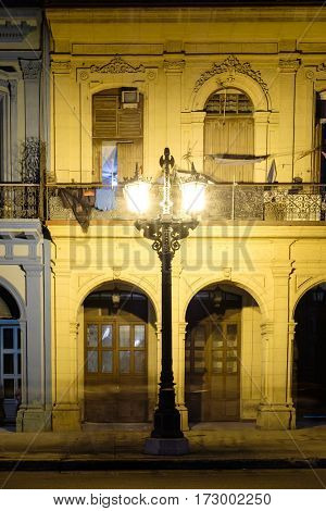 Old buildings in downtown Havana illuminated at night by a street lamp