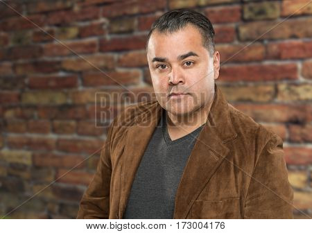 Handsome Young Hispanic Male Headshot Portrait Against Brick Wall.