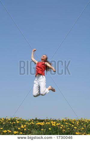 Smiling Happy Girl Jumps In Flowering Field