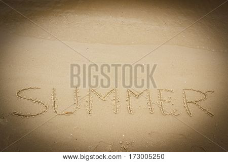 Summer written on sand at the beach by the sea concept of vacation time
