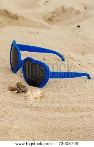 Blue Sunglasses Shaped Heart With Shells On The Sand