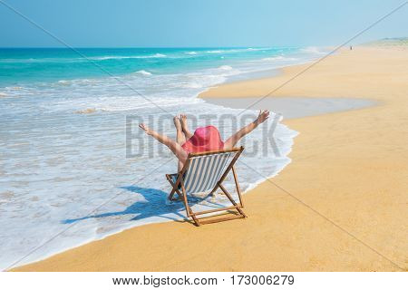 Happy woman in red sunhat on the morning beach sitting on deckchair with hands up.Vacation and travel concept.