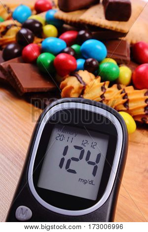 Glucose Meter With Heap Of Sweets On Wooden Surface, Diabetes And Unhealthy Food