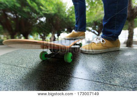 young skateboarder legs riding skateboard at city skatepark