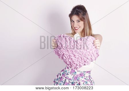 Lovely girl with a pink heart shaped cushion smiling looking to camera. In studio over a grey background. Shallow depth of field focus on her eyes.
