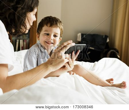 Mother sharing something on her phone to a son.