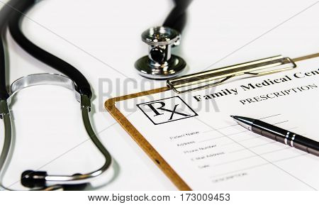 Prescription form and stethoscope on white doctors table. Medicine doctor's working table. Focus on stethoscope. Doctor care. Clinic doctor. Office doctor. Technology doctor. Doctor concept. Doctor desk. Doctor room.