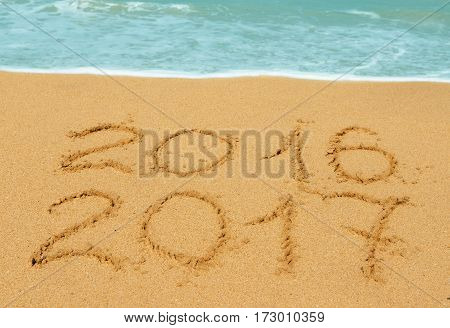 digits 2016 and 2017 on the beach - concept of new year and passing of time