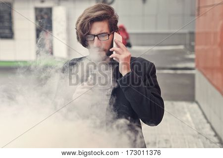 Young hipster man with a beard and glasses smokes an electronic cigarette. He says on his cell phone. Youth fashion. Delicious pairs. A cloud of steam. Business meeting