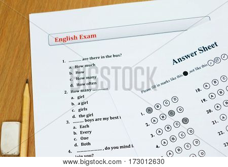 english exam and answer sheet on wooden table