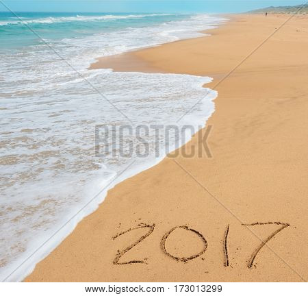 digits 2017 on the sand seashore - concept of new year and passing of time