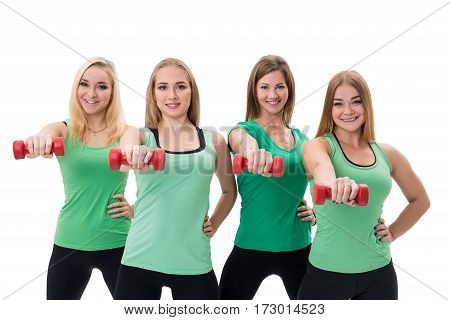 Pretty sportswomen in green tops and black leggings posing in studio with red dumbbells in their hands