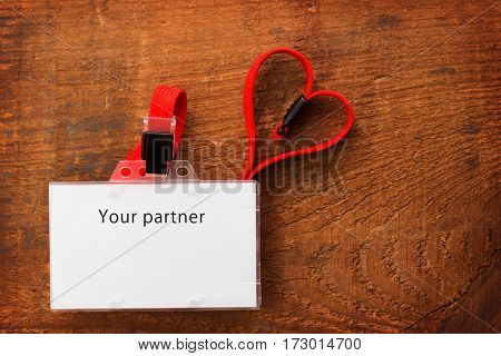 Blank ID card or security pass with red neck strap forming a shape of a heart, on rustic wooden background. WIth the word