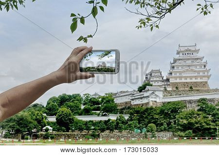 Tourist use mobile phone to take photo the Himeji castle for share to social network.