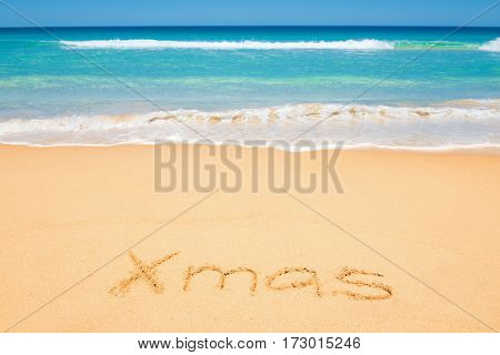 Xmas message on the beach sand - Christmas holiday vacation and travel concept