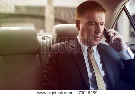 Businesswoman on the phone on backseat of the car