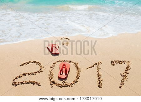 Red flip flops and digits 2017 on the beach sand.Concept of summer vacations new year and Christmas