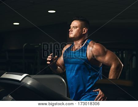 Young handsome athletic man in sportswear running on treadmill at gym