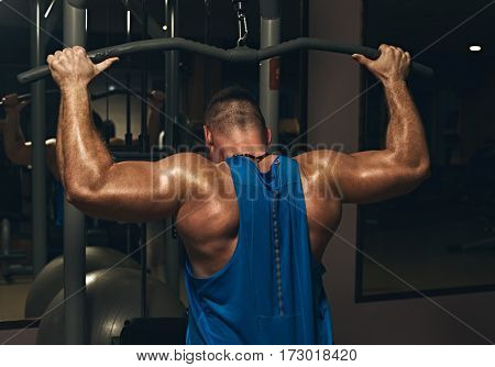 Back view of strong bodybuilder pumping up muscles at gym