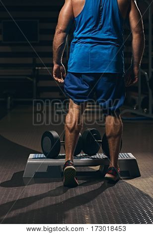calf muscles of healthy muscular man going to do exercises with dumbbells