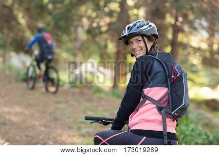 Portrait of female biker with mountain bike in countryside