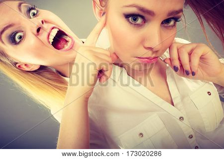 Conflict bad relationships friendship difficulties. Two young women having argument. Angry fury girl screaming at her friend or younger sister female closing his ears not listening