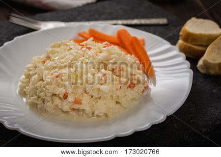 Fresh salad coleslaw of cabbage and carrots on stone plate
