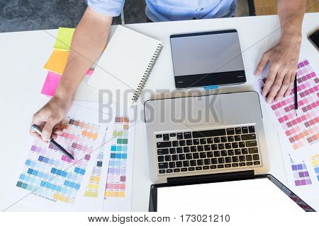 Top View Of A Young Graphic Designer Working On A Desktop Computer And Using Some Color Swatches, To