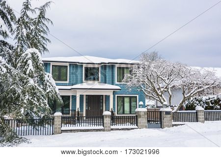 Entrance of family house with metal fence and front yard in snow. Residential house on winter cloudy day
